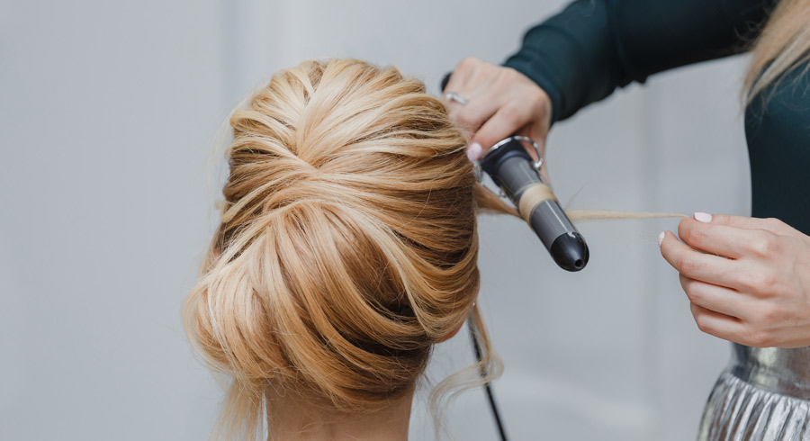 Closeup of professional hairdresser hands doing beauty hairstyle a la french twist